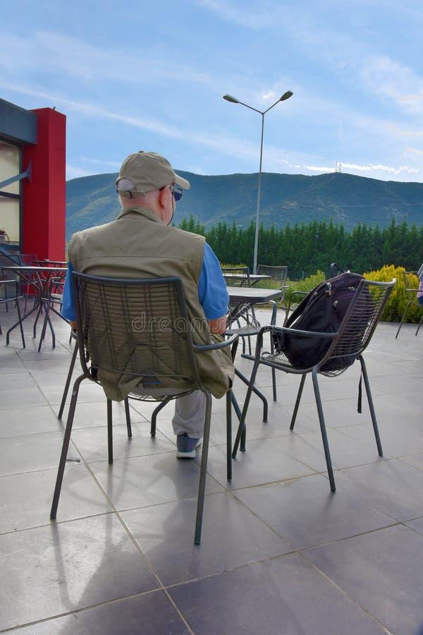 Mannen tar ett avbrott på en terrass som tycker om sikten på berget arkivfoto