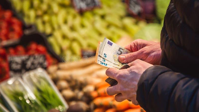 Mannen tar pengar ut från plånboken på marknad arkivbilder