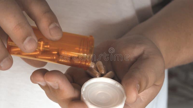 Mannen tar preventivpillervitaminer eller förgiftar upp minnestavlor i handen från preventivpillerflaskan, slut fotografering för bildbyråer