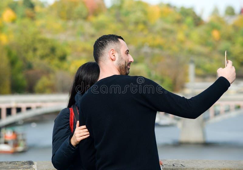 Mannen tar selfie av honom och hans flicka nära den Vltava floden och broar nära det Prague centret, den Prague Tjeckien royaltyfri foto