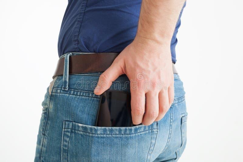 Mannen tar ut telefonen från bakfickan av jeans royaltyfria bilder