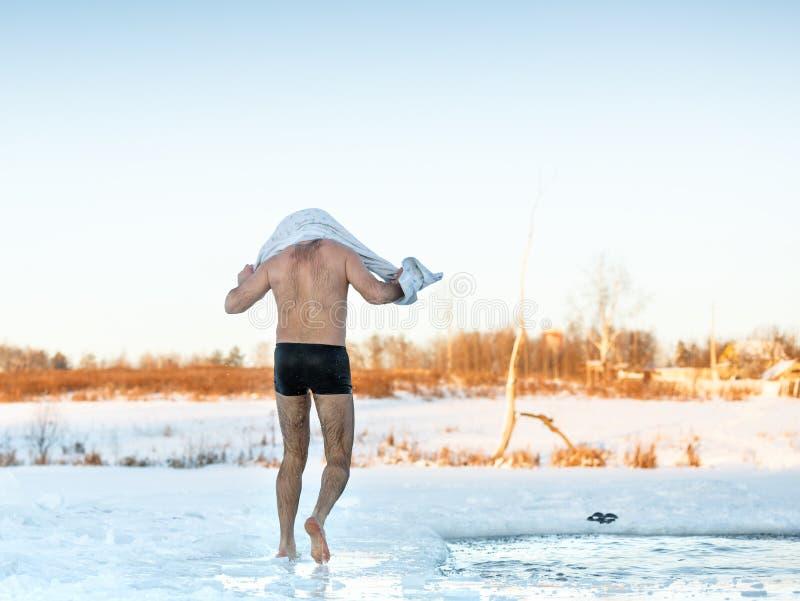 Mannen torkar handduken, når han har simmat, i att frysa hålet royaltyfria foton