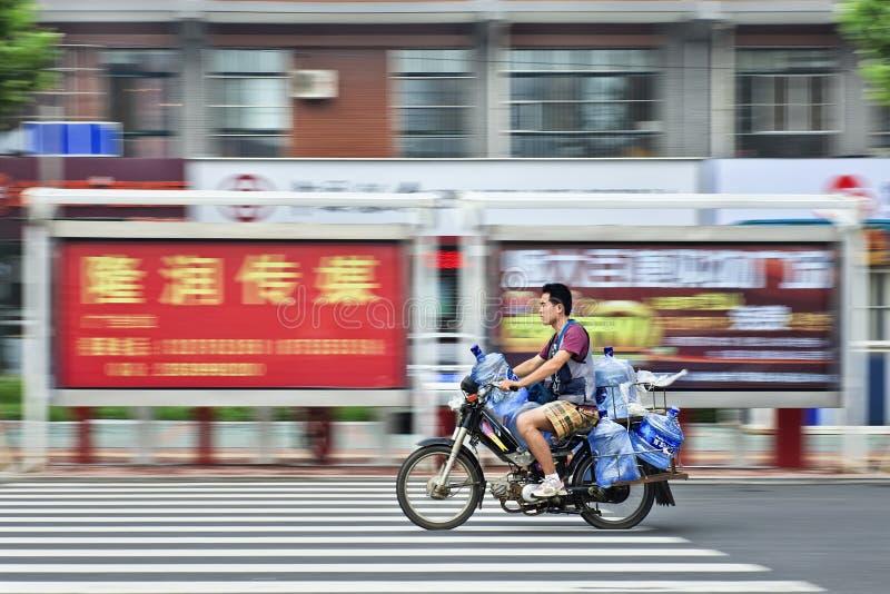 Mannen transporterar vattenbehållare på en motorcykel, Yantai, Kina arkivbilder