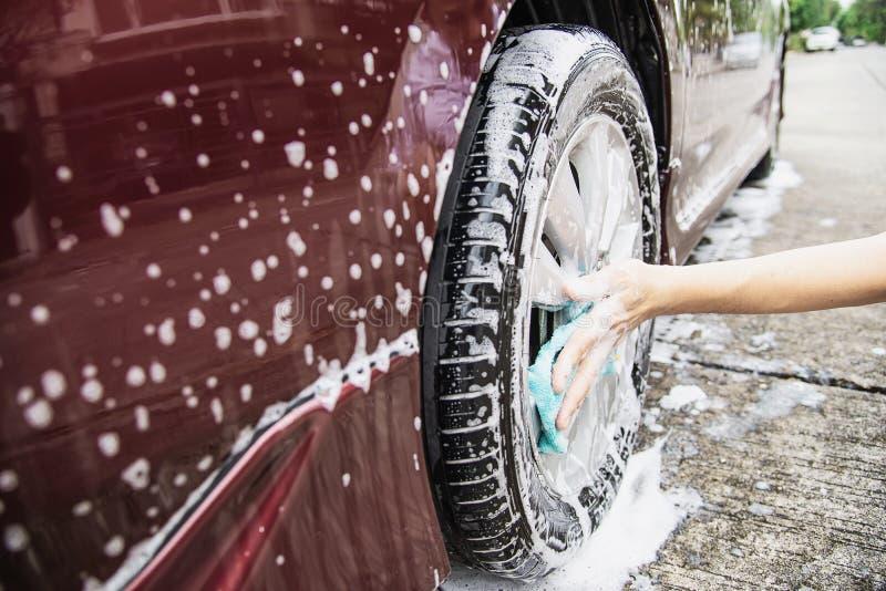 Mannen tvättar bilen genom att använda schampo royaltyfri fotografi