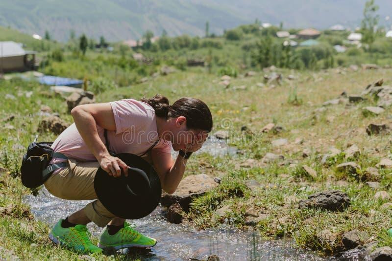Mannen tvättar hans framsida i rent flodvatten royaltyfri bild