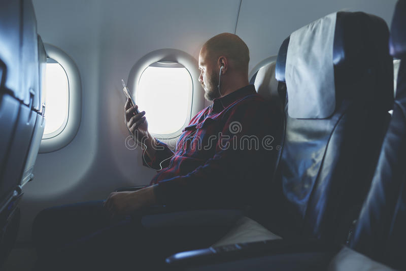 Mannen tycker om hans favorit- musik via celltelefonen, medan flyger i ett flygplan arkivbild