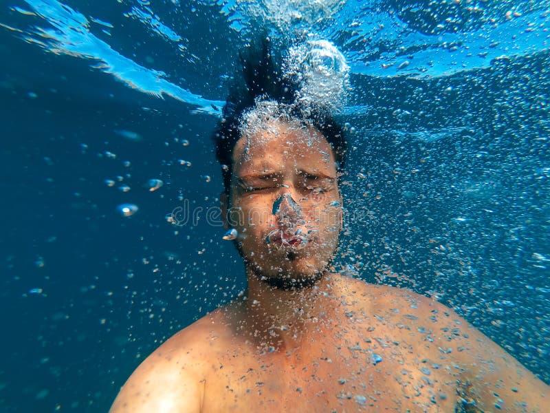 Mannen under vatten sjunker för att bottna och frigörarbubblor av syre royaltyfri foto