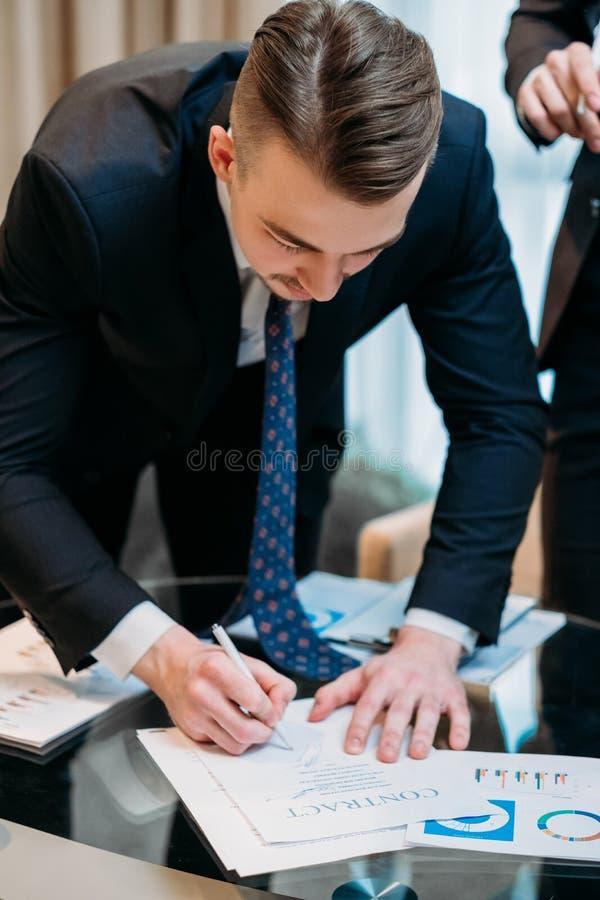 Mannen undertecknar bokslut för avtalsaffärspartneravtal royaltyfri foto