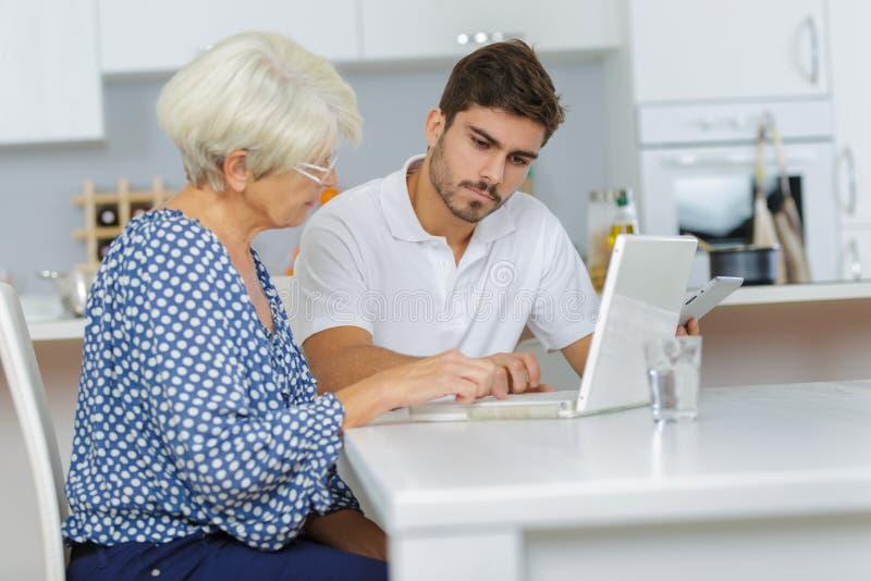 Mannen undervisar den äldre kvinnan hur man arbetar genom att använda bärbara datorn arkivfoton