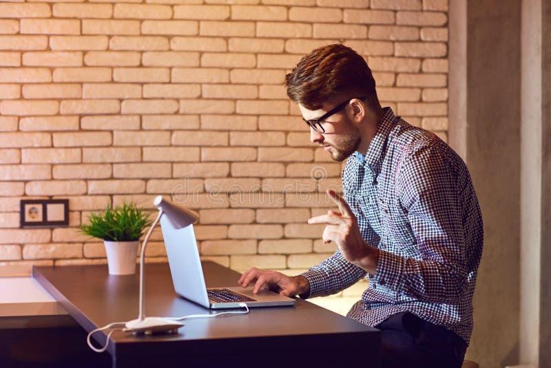 Mannen uppsökt freelancer med en bärbar dator arbetar i aftonen arkivfoto