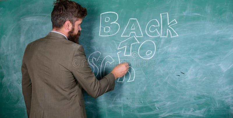 Mannen uppsökte läraren missa hans arbete under semester Läraren nära den svart tavlan rymmer krita skriver inskriften tillbaka t royaltyfri foto