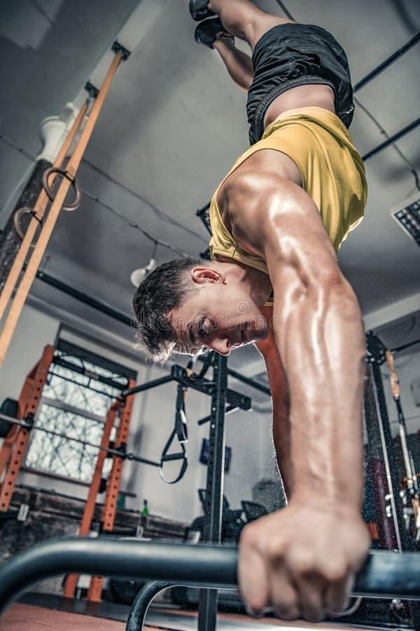 Mannen utför handstanding på idrottshallen royaltyfri foto