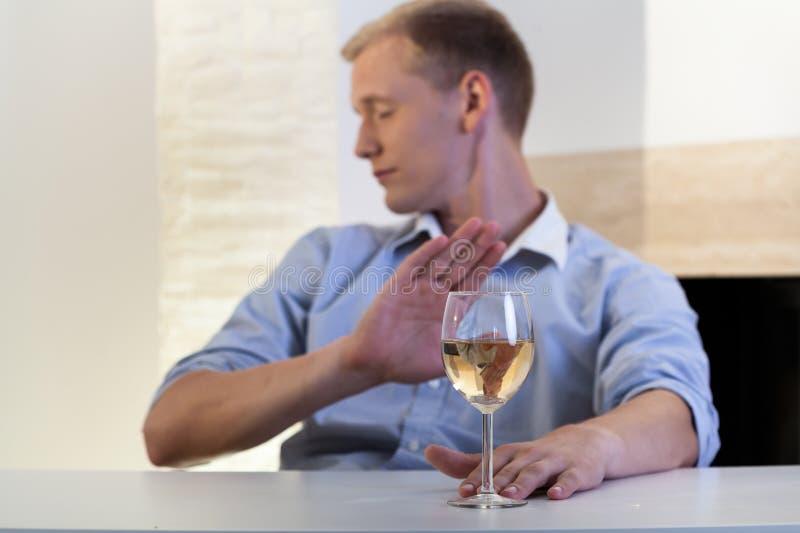 Mannen vägrar att dricka ett exponeringsglas av vin royaltyfri foto