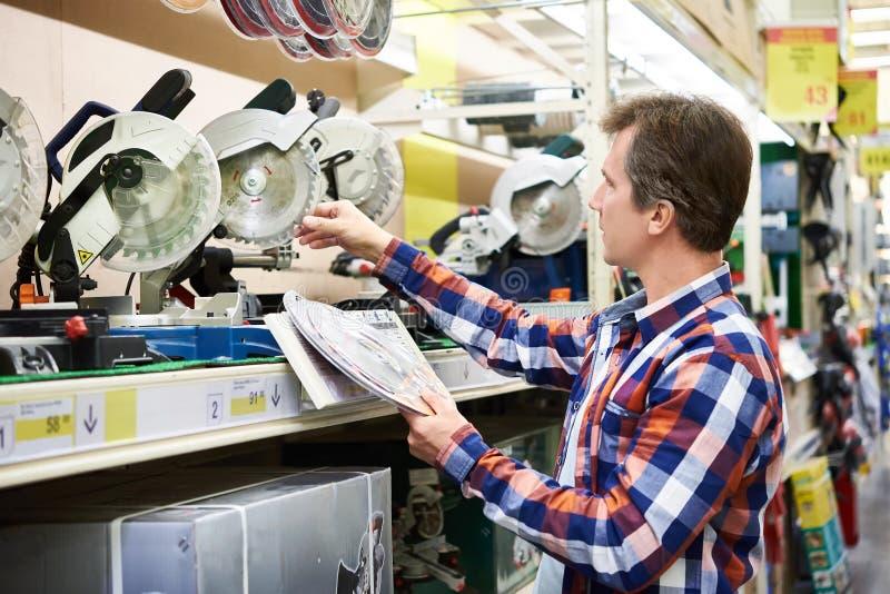 Mannen väljer bladet för elektriska mitrasågar i lager arkivbilder