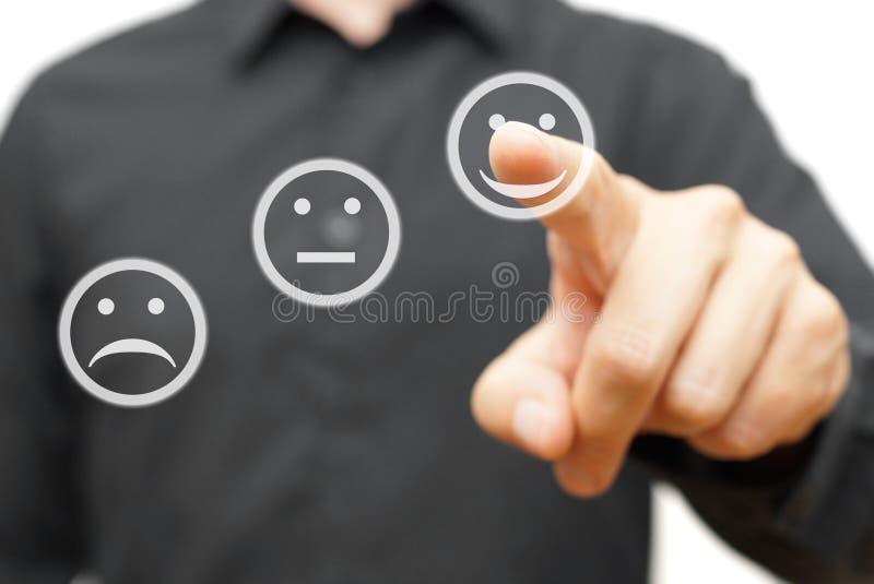 Mannen väljer den lyckliga positiva leendesymbolen, begrepp av satisfactien royaltyfria foton