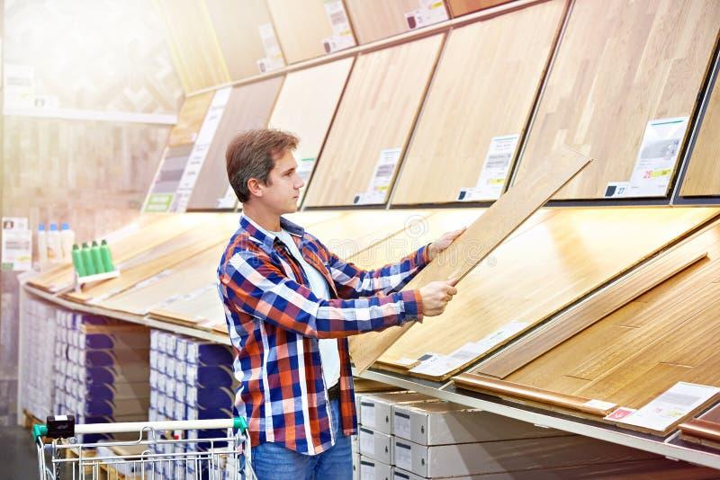Mannen väljer golvtilja för hem- renovering arkivfoton