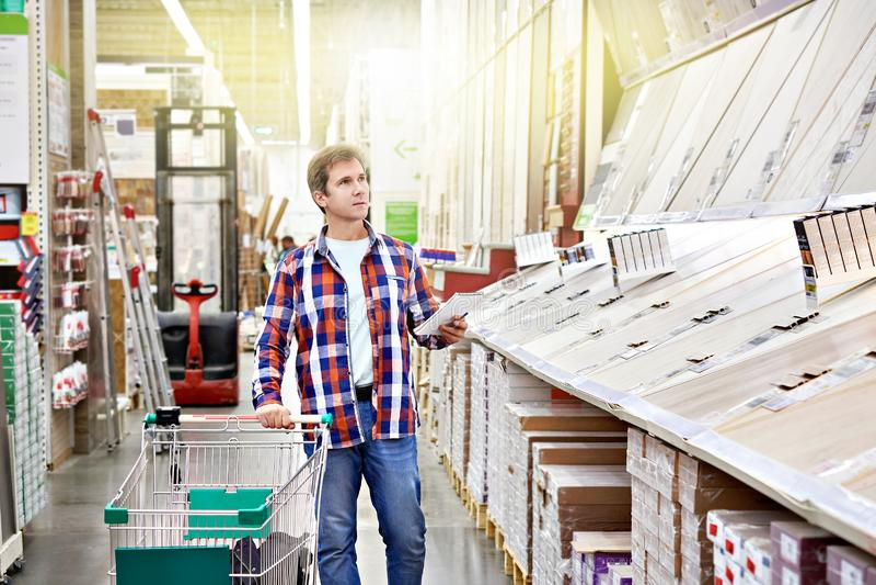 Mannen väljer golvtilja för hem- renovering royaltyfria bilder