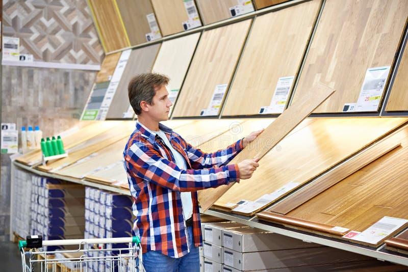 Mannen väljer golvtilja för hem- renovering arkivfoto