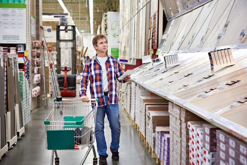 Mannen väljer golvtilja för hem- renovering fotografering för bildbyråer