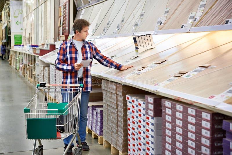 Mannen väljer golvtilja för hem- renovering arkivbilder