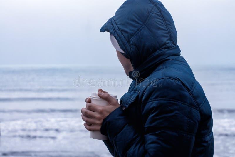 Mannen värme hans händer med takeaway kaffe arkivbilder