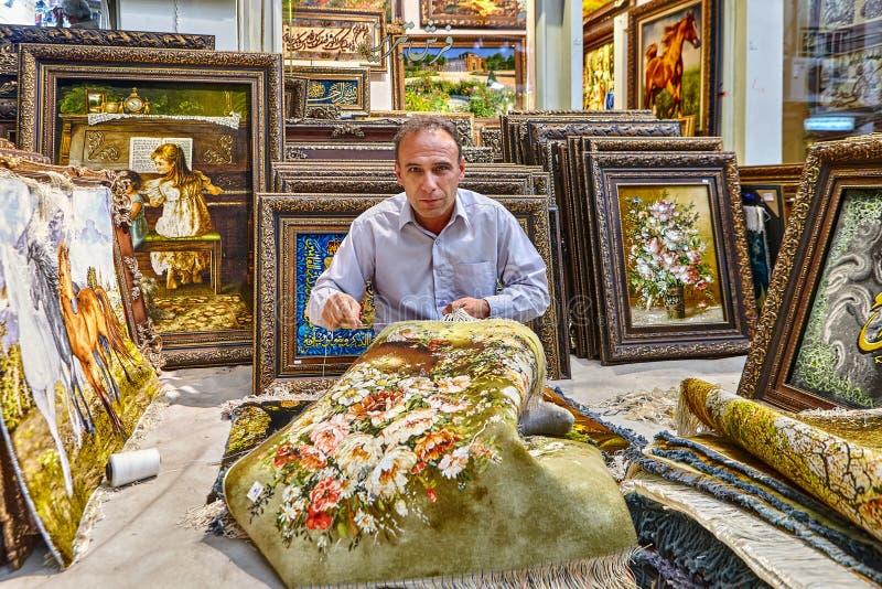 Mannen väver matta i lagret av persiska filtar, Iran royaltyfri foto
