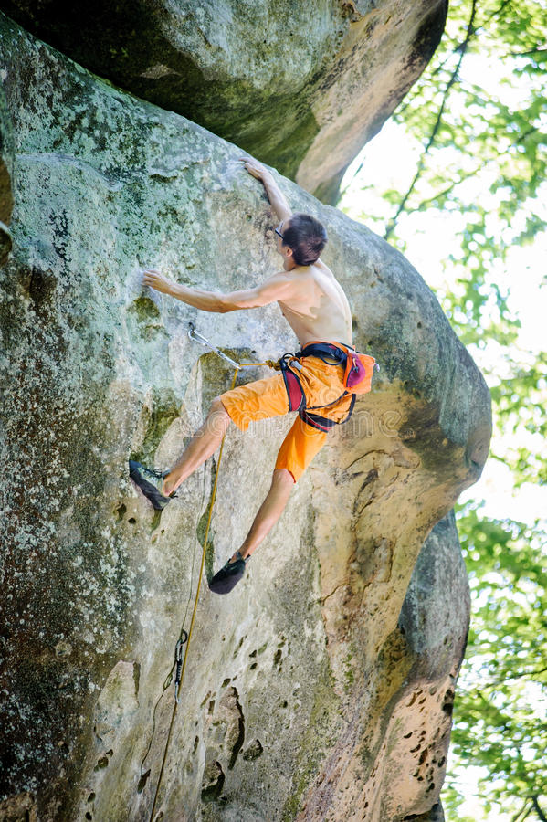 Mannen vaggar klättrareklättring med repet på en stenig vägg royaltyfri foto