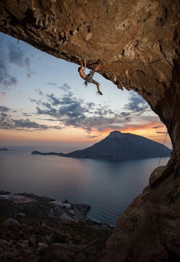Mannen vaggar klättraren på solnedgången. Kalymnos Grekland royaltyfri foto
