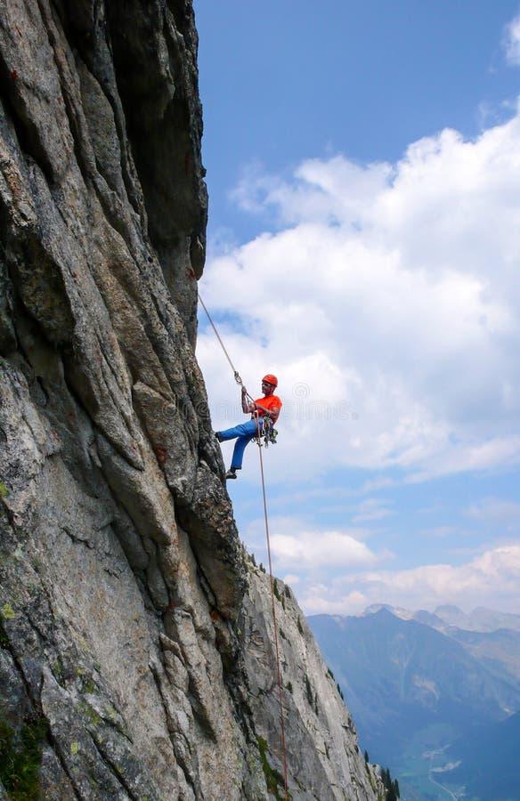 Mannen vaggar klättraren som abseiling av ett brant, vaggar klättringrutten i de schweiziska fjällängarna efter en hård klättring arkivbild