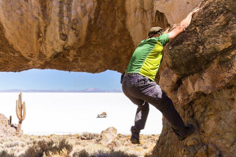 Mannen vaggar klättringstenklippan, Salar de Uyuni Bolivia royaltyfria bilder