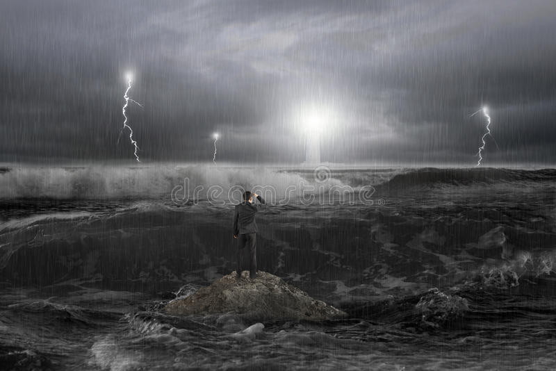 Mannen vaggar på att stirra fyren i havet med stormen arkivbild