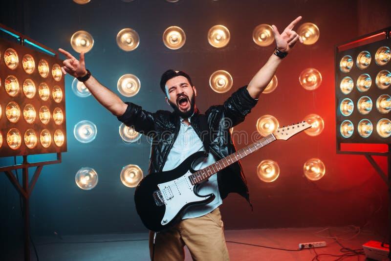 Mannen vaggar stjärnan med den electro gitarren på etappen royaltyfri foto