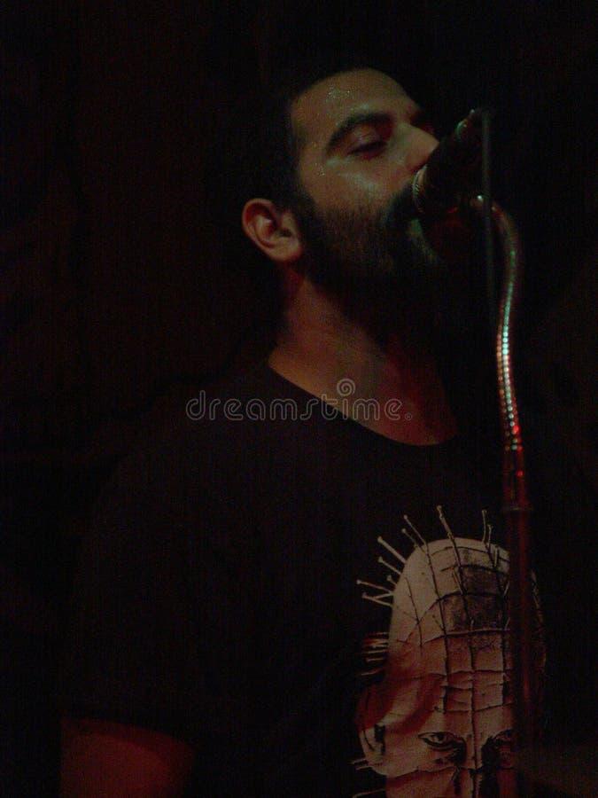 Mannen vaggar vokalisten som nästan sjunger en mikrofon på en show på natten i mörk omgivning arkivfoto
