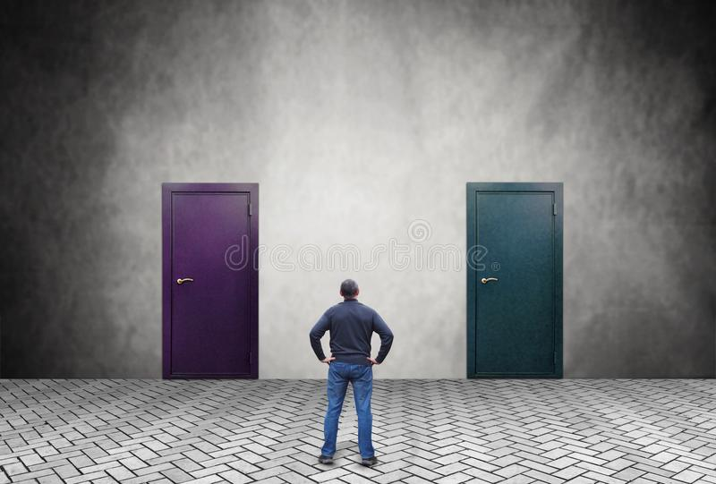 Mannen vet inte vilken av de två dörrarna han måste skriva in royaltyfri bild