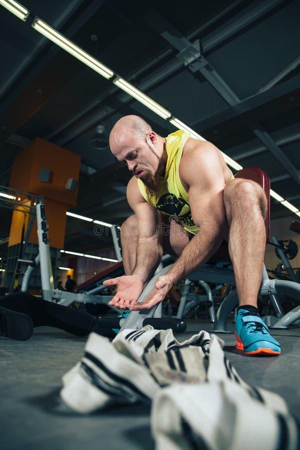 Mannen vilar i idrottshallen som har After en genomkörare royaltyfria foton