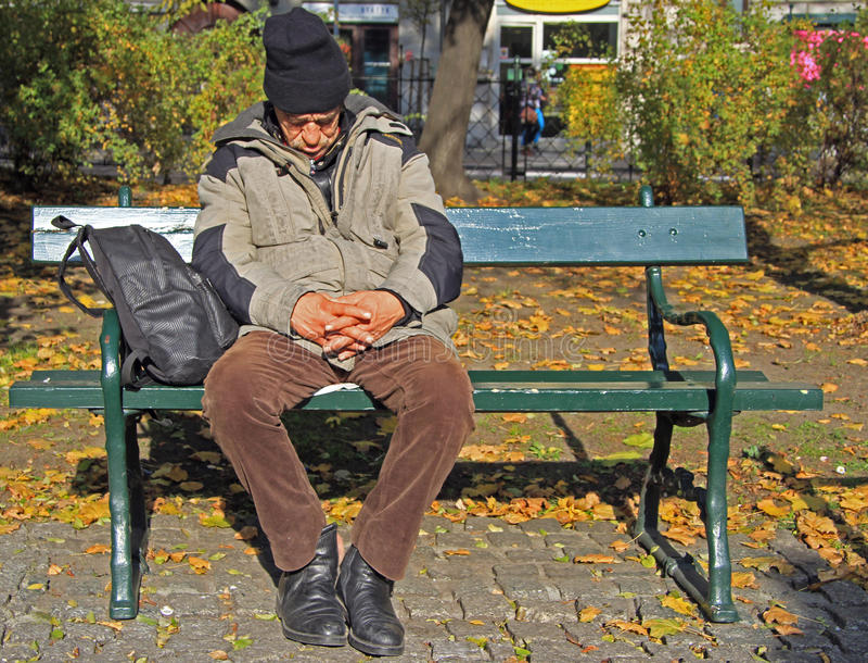 Mannen vilar på en bänk som är utomhus- i Krakow, Polen fotografering för bildbyråer