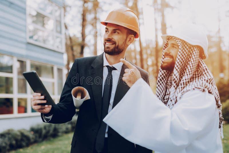 Mannen visar konstruktionsplan till den arabiska affärsmannen royaltyfri bild