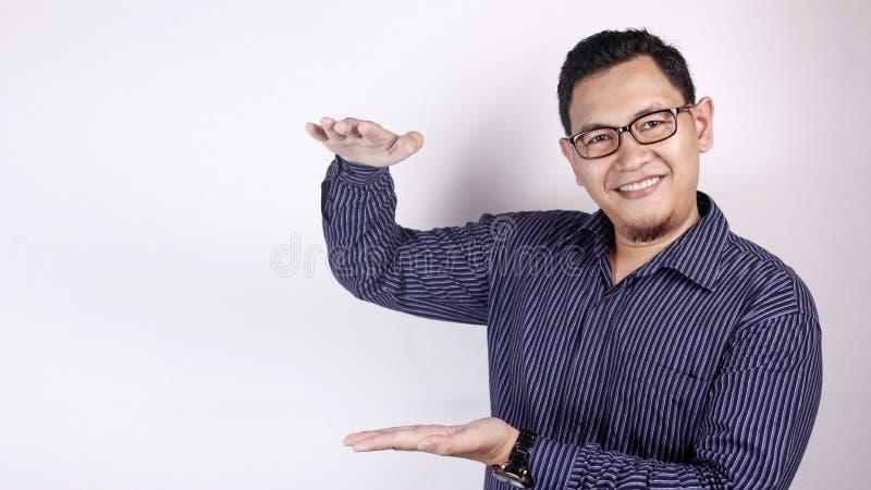 Mannen visar något mellan händer fotografering för bildbyråer