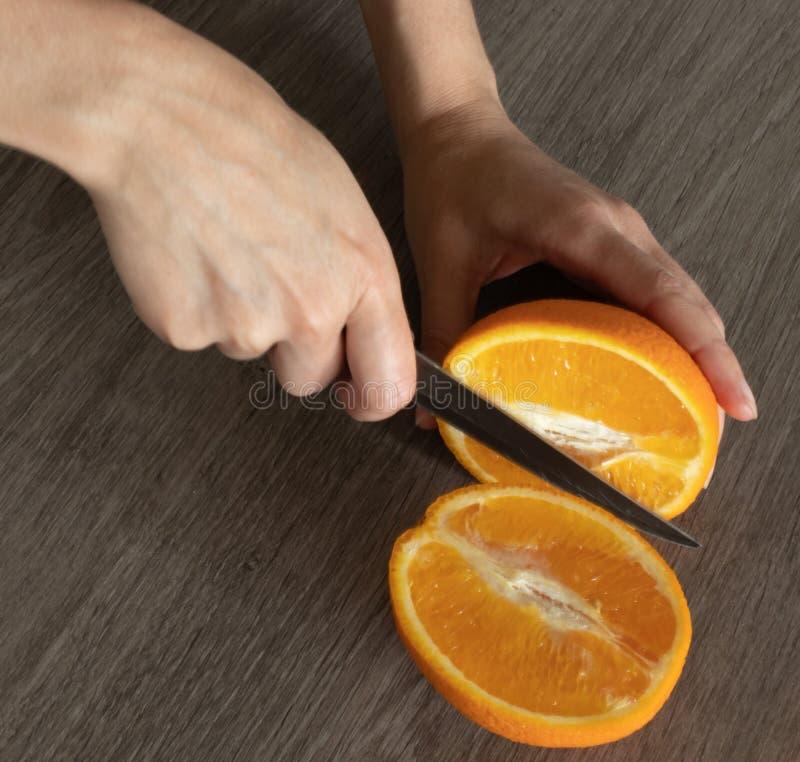 Mannens händer med en kniv klippte apelsinen i halva royaltyfri foto