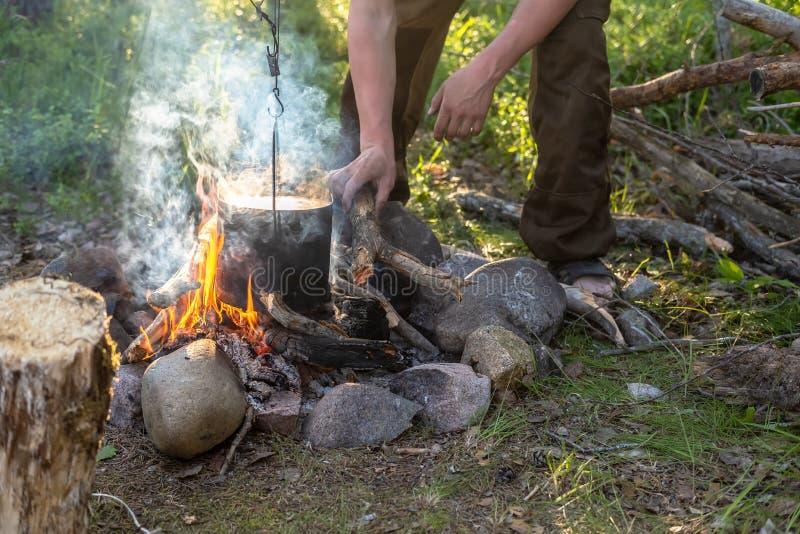 Mannens händer sätter vedträ in i brasan, som hänger över en kruka med en att förbereda matställe, på en öppen brand, på öppen lu royaltyfria foton