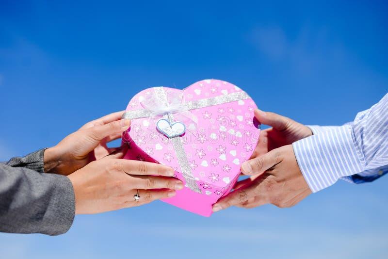 Mannens händer som ger rosa hjärta, formade asken till kvinnan royaltyfri foto