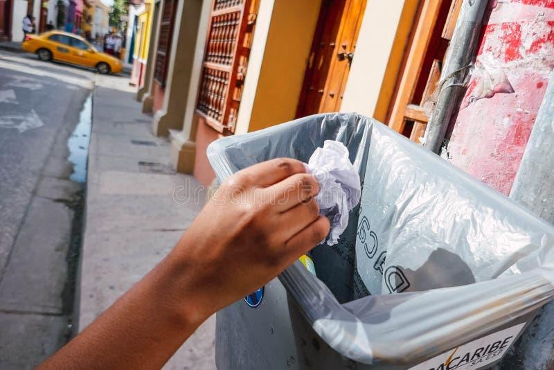 Mannens hand som kastar papper i, återanvänder facket, miljöskyddbegrepp royaltyfri foto