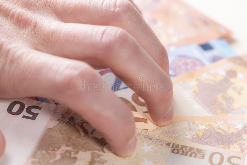 Mannens hand som vrids med girighet, krattar en grupp av eurosedlar till honom arkivfoton