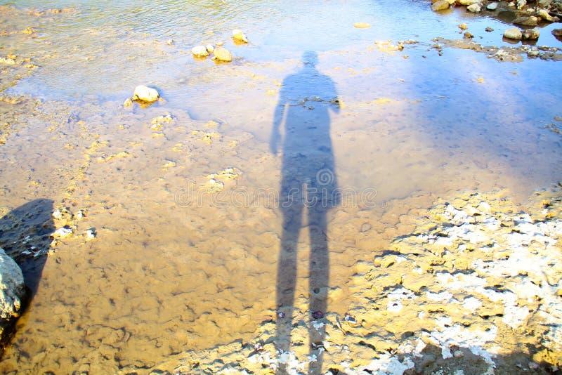 Mannens skugga reflekterade i floden på shorelinen på en ljus dag royaltyfri fotografi