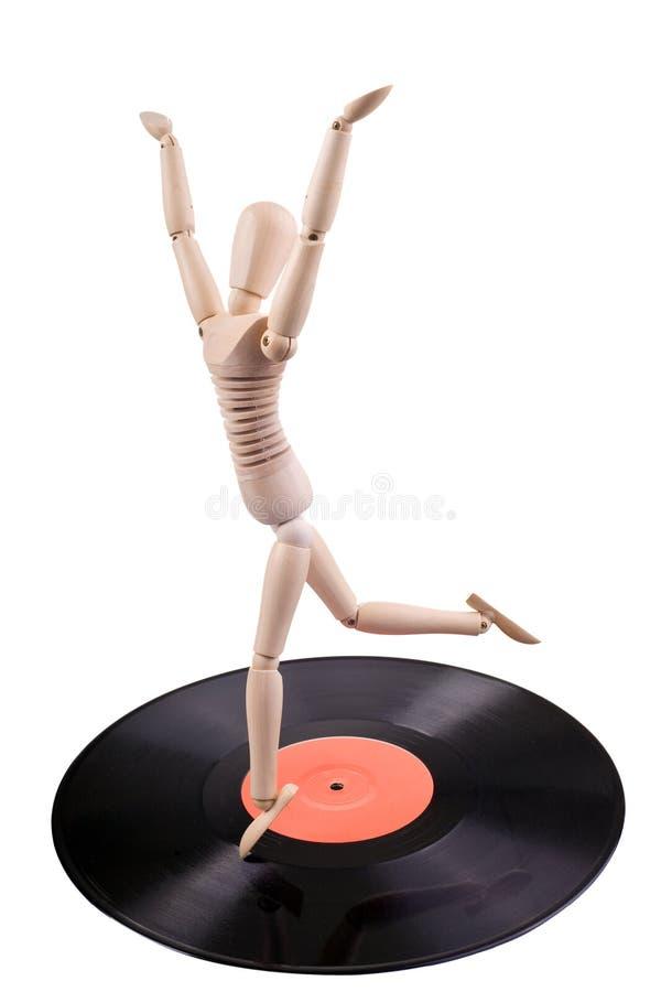 Mannequin dancing on vinyl disc. Wooden mannequin dancing on old vinyl disc royalty free stock image