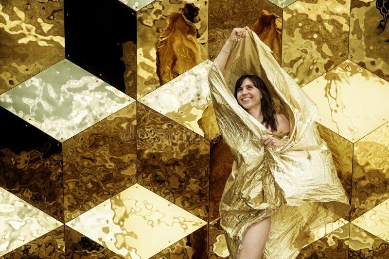 Mannequin dans la robe d'or, portrait de beauté de femme, tissu éclatant d'or de ondulation devant le fond d'or de cube images libres de droits