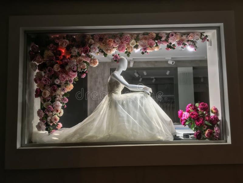 Mannequin in einem Hochzeitskleid, nachts in einem Shopfenster gekleidet stockfotografie