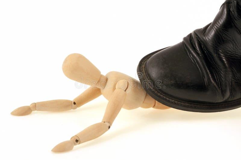 Mannequin en bois sculpté écrasé par une chaussure photos libres de droits