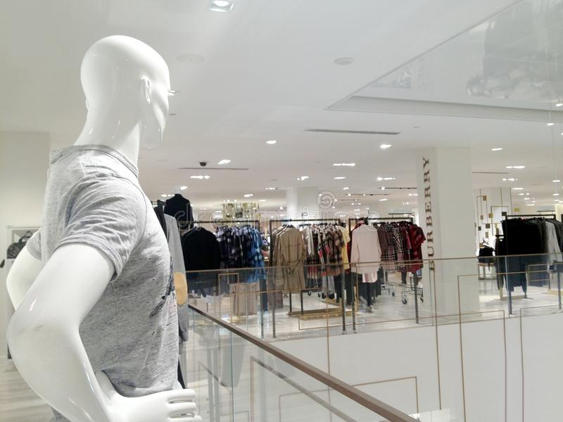 Mannequin male figure looking at Burberry fashion boutique stock image