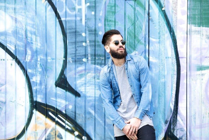 Mannequin masculin avec des lunettes de soleil posant par le graffiti photographie stock libre de droits